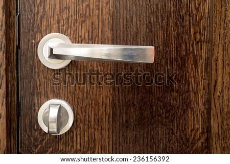 Shiny knob on brown wooden door - stock photo