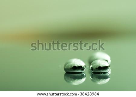 Shiny Mercury drops on a green background - stock photo