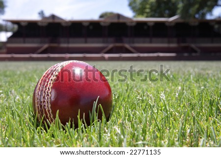 Shiny new cricket ball on grass in front of grand stand. - stock photo