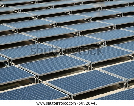 Shiny, new solar panels on a concrete rooftop. - stock photo