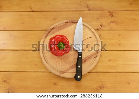 Shiny red bell pepper with a sharp kitchen knife on a wooden chopping board - stock photo