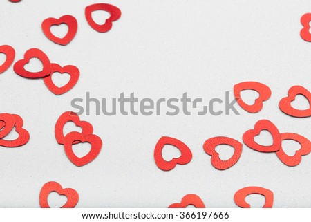 Shiny red heart confetti on sparkling white surface. - stock photo