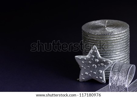 Shiny silver star and Christmas candle on a dark background - stock photo