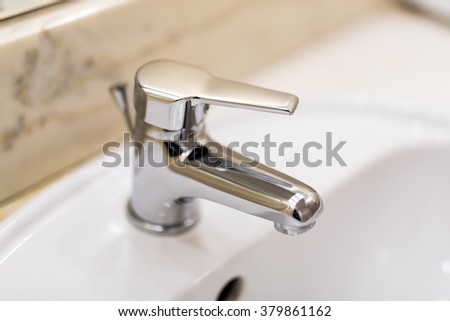 Shiny stainless steel faucet with chrome water tap - stock photo