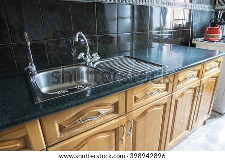 Shiny stainless steel sink on kitchen - stock photo