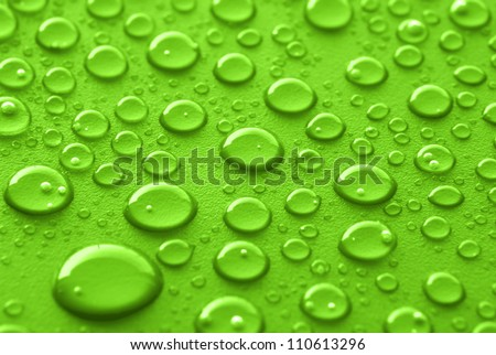 Shiny water drops sprayed on textured green surface. - stock photo