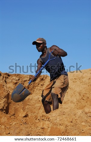 SHINYANGA, TANZANIA-MARCH 18: An unidentified miner shovels sand March 18, 2010 in Shinyanga, Tanzania. Tanzania is the third gold producer in Africa after Ghana and South Africa. - stock photo