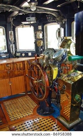Ship control bridge interior. Wooden captains helm and navigation equipment on the old  sail vessel. Navigator cabin with navigation instruments, rudder and compass. - stock photo