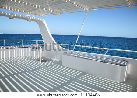 ship deck with striped  shadowo on blue sea background - stock photo