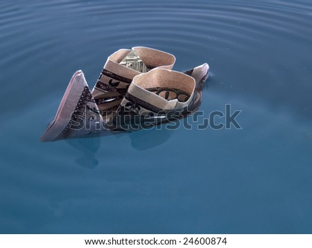 Ship model made of 50 dollar bank note sinks in blue water - stock photo