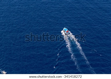Ship navigates into beautiful blue water near Santorini island, Aegean sea in Greece. - stock photo
