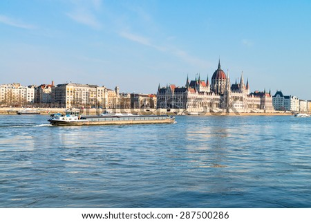 Ship passes Parliament building in central Budapest on a bright day - stock photo
