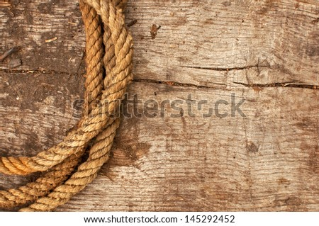 Ship rope and weathered wood background, top view