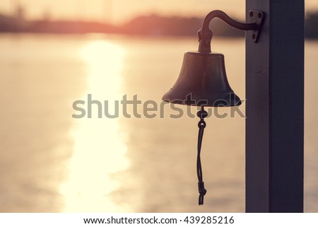 Ship's bell at sunset on the sea. - stock photo