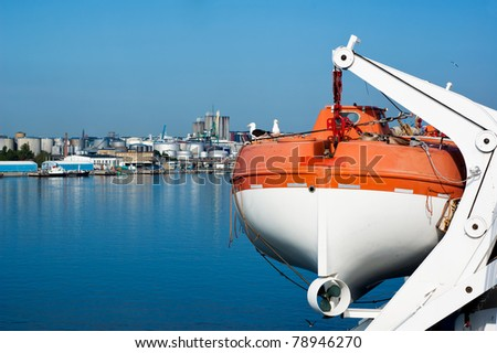 Ship's lifeboat at the industrial port - stock photo