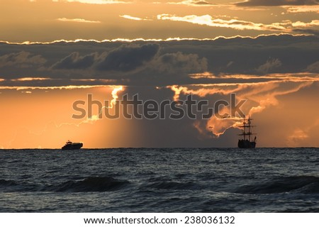 Ship silhouettes on sea horizon against red cloudy sky just before sunset, Baltic Sea, Poland - stock photo