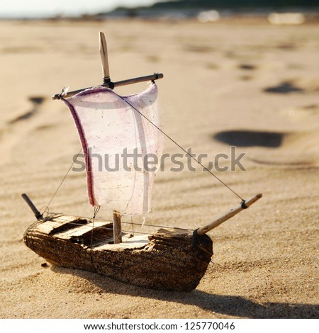 ship toy model on the beach - stock photo