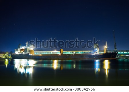 Ship under loading stone at night in Port of Gdansk, Poland. - stock photo