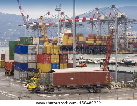Shipping containers being trucked away from dock - stock photo