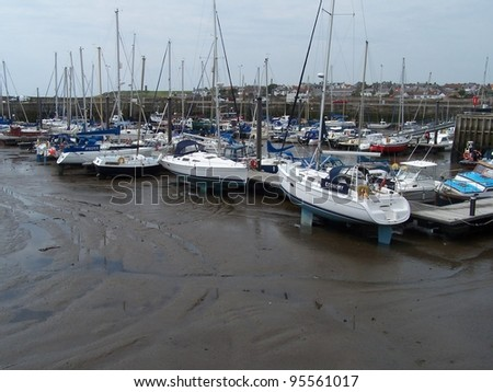 Ships on seafloor in a harbor at low tide - stock photo