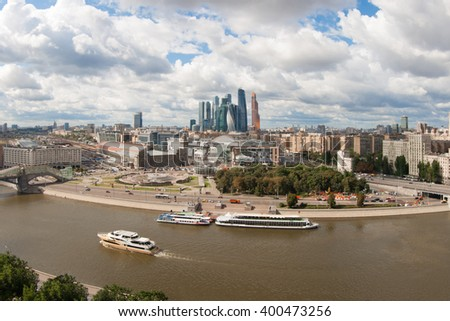 Ships sail on river at summer day in Moscow, Russia, Skyscrapers far away - stock photo