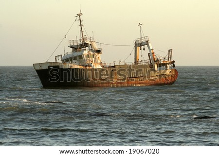 shipwreck at sunset in ocean - stock photo