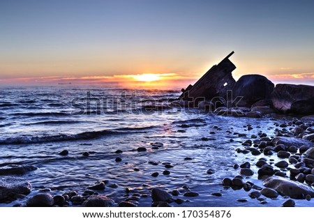 Shipwreck Dawn.  Sun rises over a misty Lake Huron with the silhouette of a shipwreck in the foreground . - stock photo