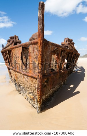 Shipwreck on Fraser Island. Bow of the wreck stands tall, the Maheno lies rusting at the tidal edge. - stock photo