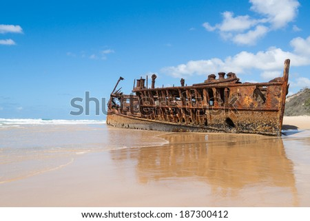 Shipwreck on Fraser Island. The wreck of the Maheno lies rusting at the tidal edge. - stock photo