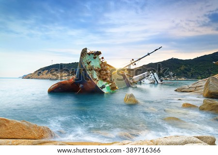 shipwreck or wrecked cargo ship abandoned on sea bay - stock photo