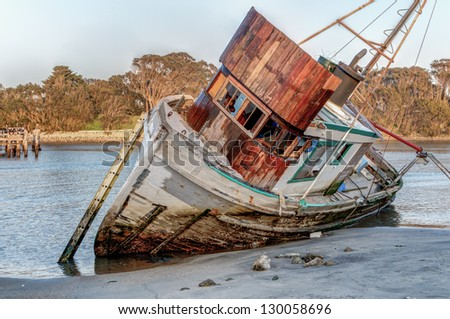 Shipwrecked Vessel Washed Ashore at Moss Landing, California. - stock photo