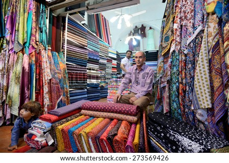 SHIRAZ - APRIL 15: Unknown man trades traditional iranian fabrics in market (Vakil Bazaar) in Shiraz, Iran on April 15, 2015. Vakil Bazaar is the most important tourist attraction in Shiraz, Iran. - stock photo