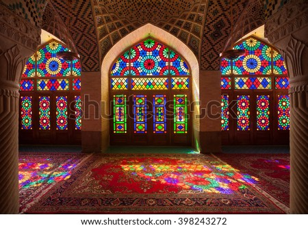 SHIRAZ, IRAN â?? SEPTEMBER 18, 2014: Interior of ornamental Nasir Al-Molk Mosque with colorful stained glass windows. It is also called Pink Mosque and was built from 1876 to 1888 during Qajar rule. - stock photo