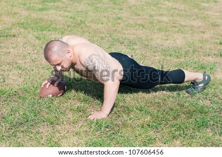 Shirtless american football player doing push-ups with ball on the playfield - stock photo