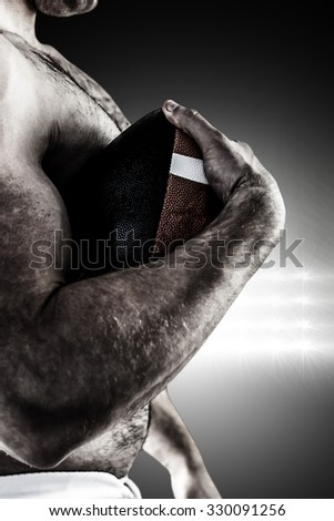 Shirtless American football player with ball against spotlight