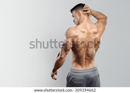 Shirtless athletic man turned back on white background. - stock photo