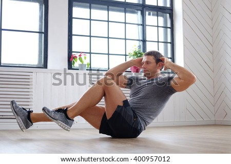 Shirtless athletic middle age man doing stomach workouts on a floor. - stock photo