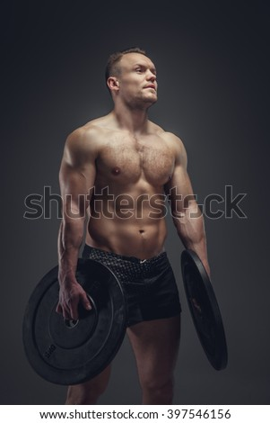 Shirtless bodybuilder holds lifting weights.