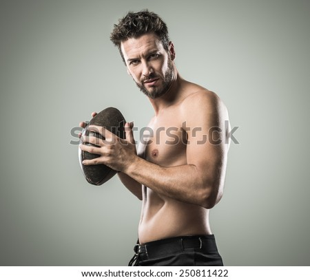 Shirtless confident footbal player holding ball and showing his muscular body - stock photo