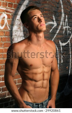 Shirtless fit young man in alley looking up - stock photo