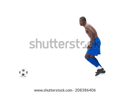 Shirtless football player moving to the ball on white background - stock photo