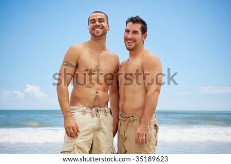 Shirtless gay couple standing on a beach - stock photo