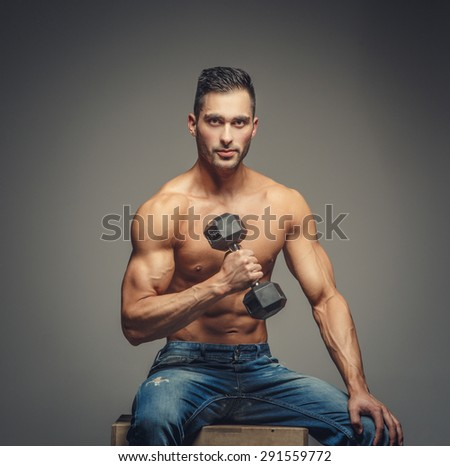 Shirtless guy in blue jeans sitting on podium. Isolated on grey background.