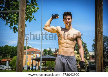 Shirtless handsome fit athletic young man doing bicep pose outdoor, happy and proud of his muscular body - stock photo