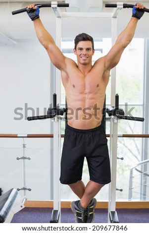 Shirtless male body builder doing pull ups at the gym - stock photo