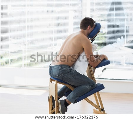 Shirtless male patient sitting on massage chair in hospital - stock photo