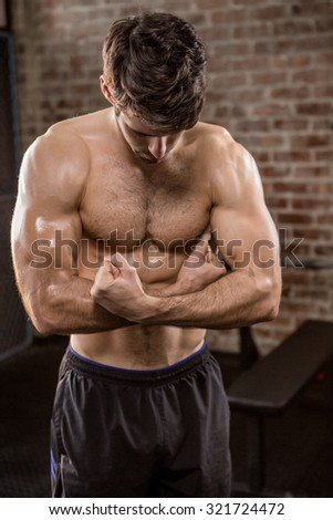 Shirtless man showing his body at the gym - stock photo