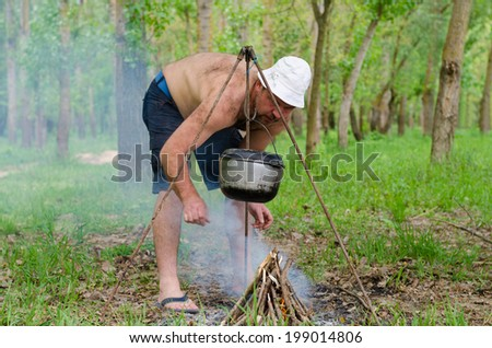 Shirtless man starting a cooking fire in a campsite lighting the pyramid of kindling as an iron cauldron swings from a frame above - stock photo