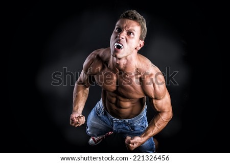 Shirtless Muscle Man with Pointed Teeth Transforming into Werewolf in Studio with Black Background - stock photo