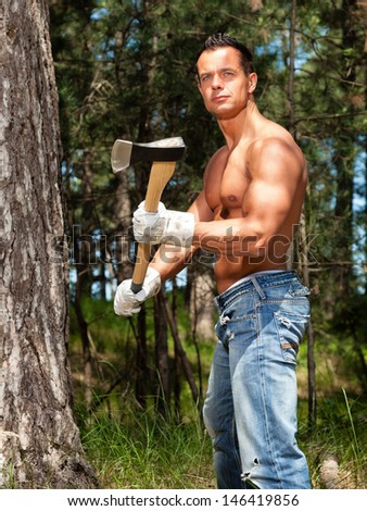 Shirtless muscled fitness lumberjack man with axe in forest.